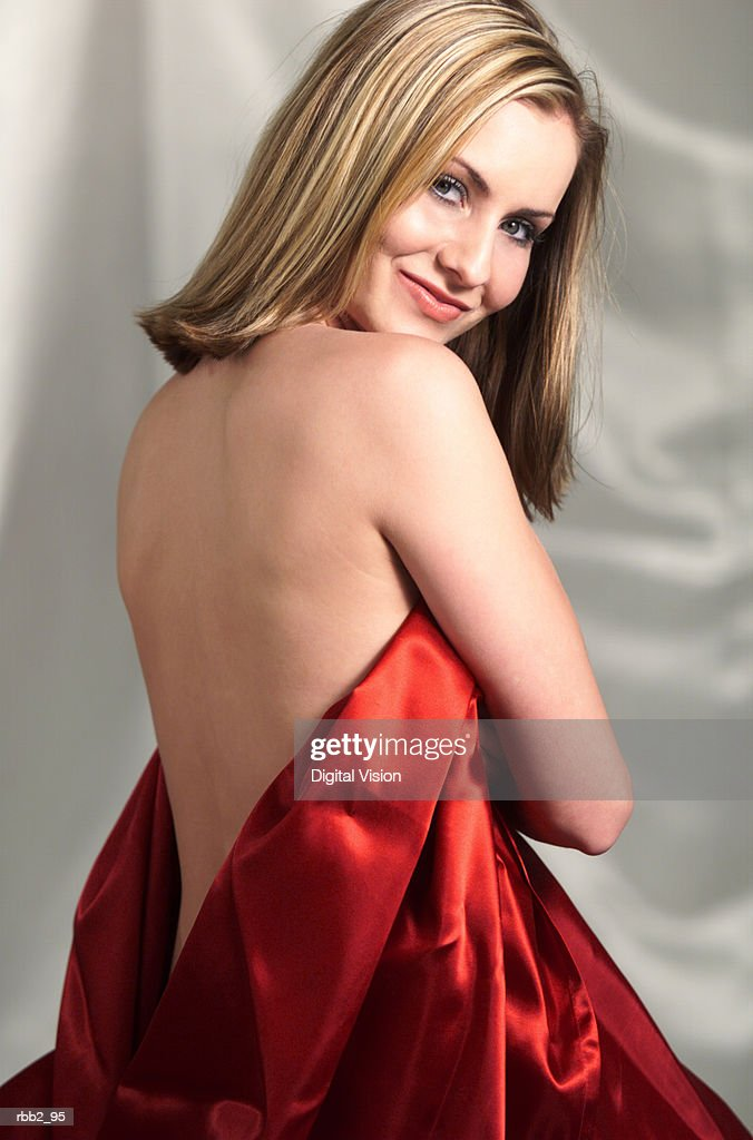 a young caucasian blonde wrapped in red satin sheet exposing her back turns around and smiles : Stockfoto
