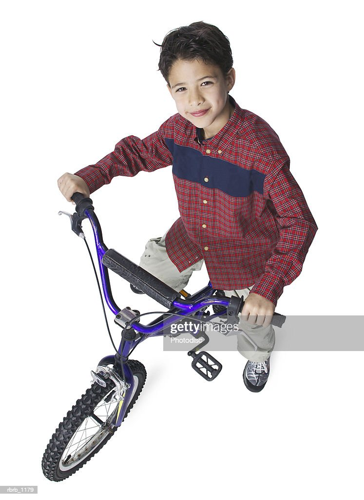 a young caucasian boy in a red plaid shirt sits on his bike and smiles up at the camera : Stockfoto