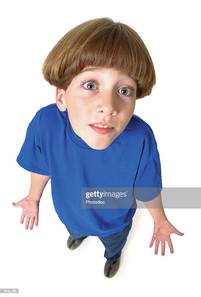 a young caucasian boy in jeans and a blue shirt shrugs his shoulders and looks quizzically up into the camera : Foto de stock