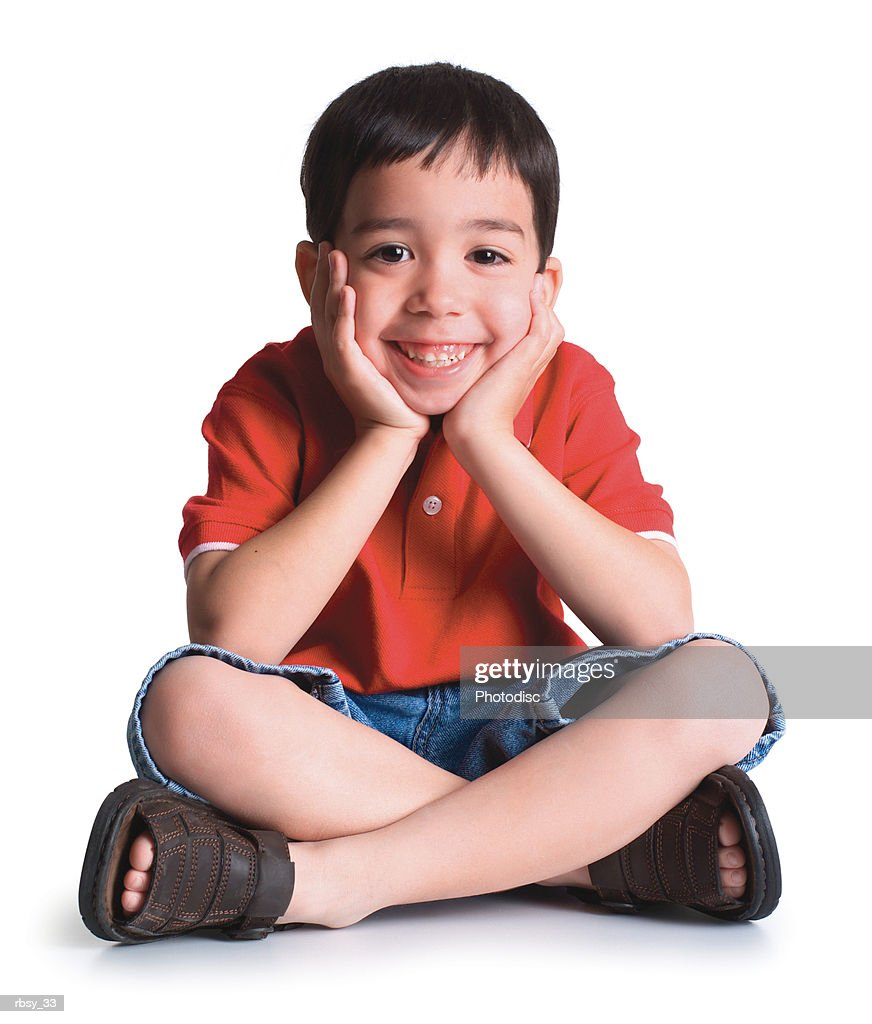 a young caucasian boy in shorts and red shirt sits down and puts his face in his hands : Foto de stock