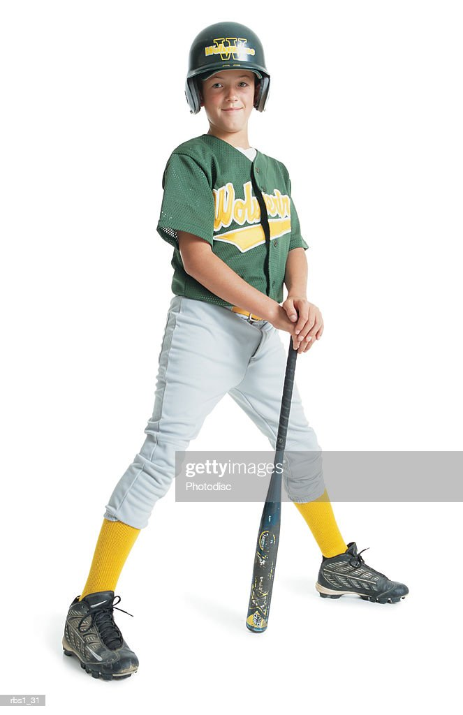 a young caucasian boy is wearing a green little league uniform and stands leaning on a bat while wearing a green batting helmet : Foto de stock