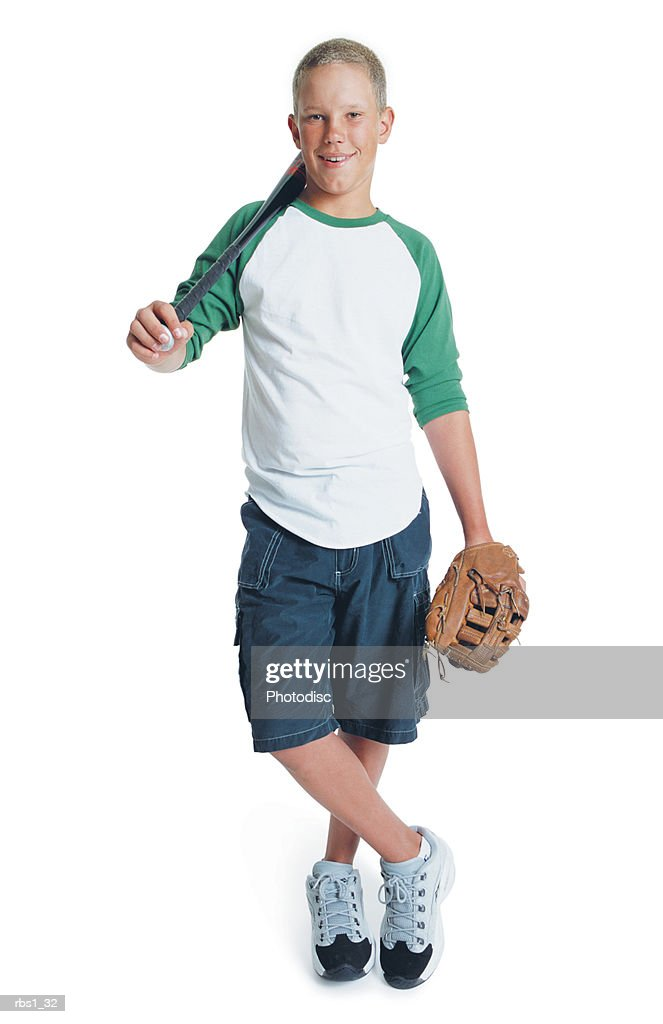 a young caucasian boy is wearing blue shorts and a t-shirt as he stands crosslegged with a baseball bat over his shoulder and has a baseball glove on his hand : Foto de stock