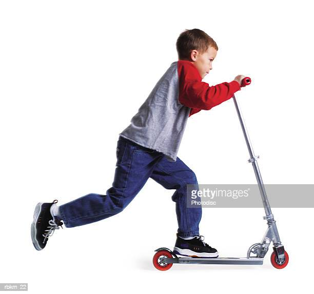 a young caucasian boy races by on his nifty scooter