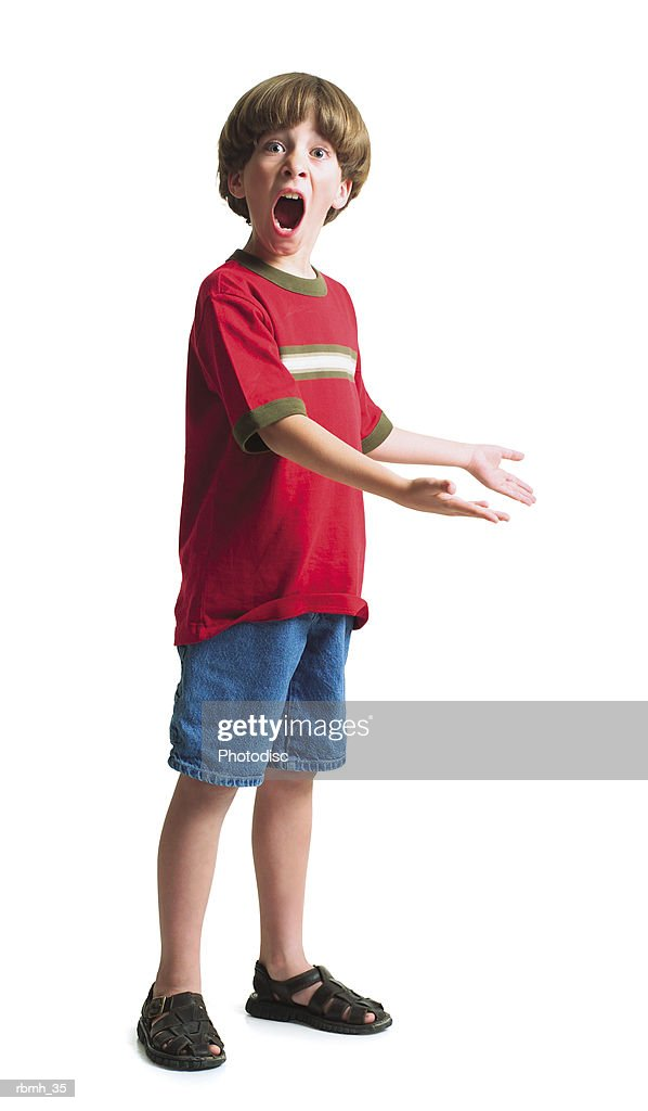 a young caucasian boy wearing jean shorts and a red shirt stands with his hands held out to the side with a look of suprise on his face : Stockfoto