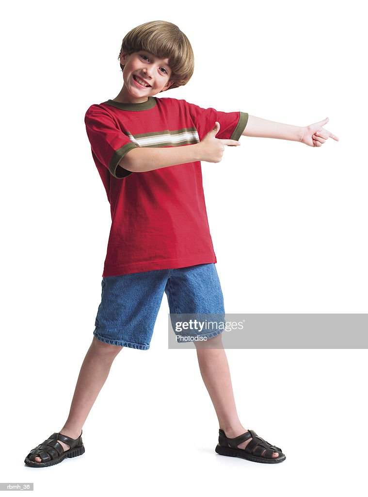 a young caucasian boy wearing jean shorts and a red shirt stands with his legs spread shoulder width apart and holds his arms out to one side indicating a product : Stockfoto