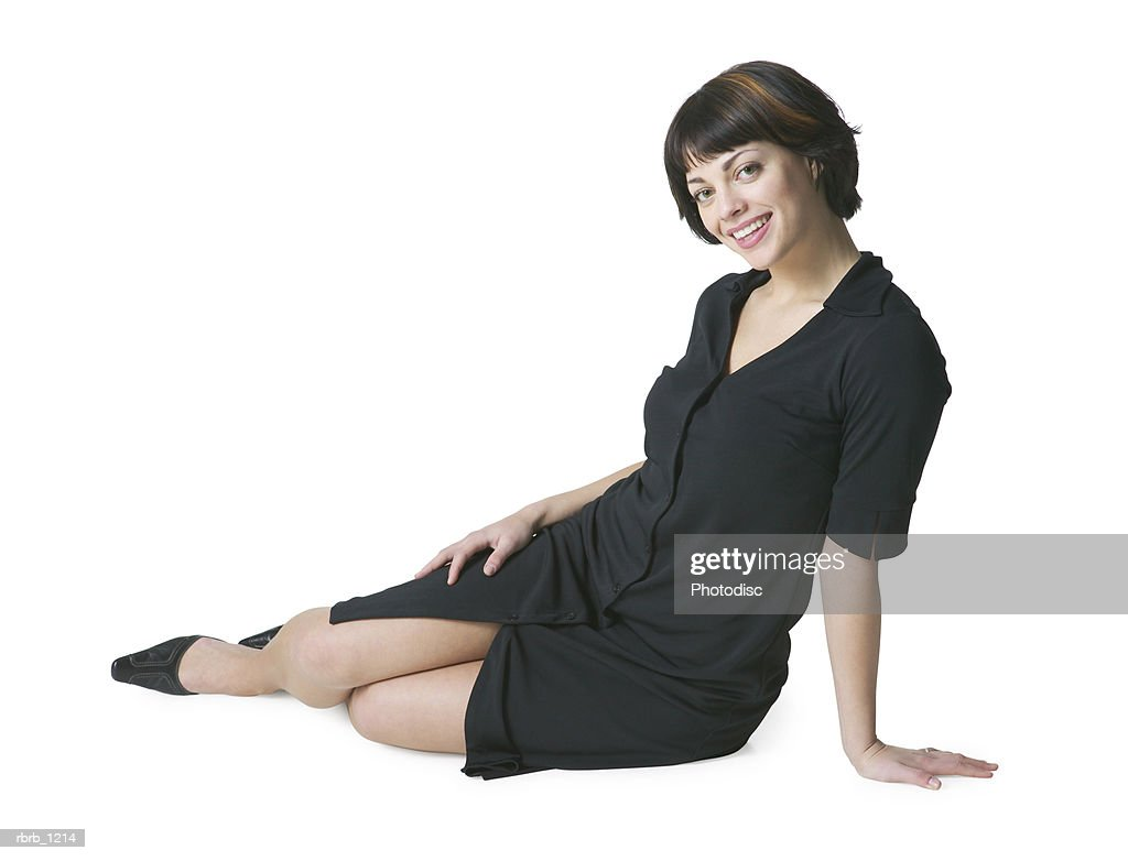 a young caucasian brunette woman in a black dress sits on her side and smiles : Stock Photo