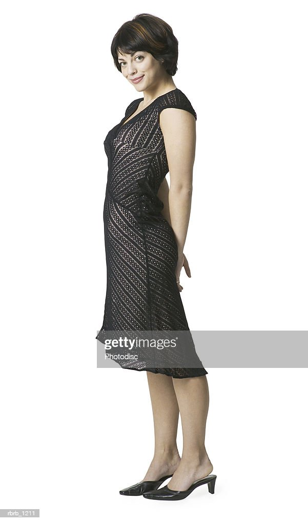 a young caucasian brunette woman in a black dress stands to the side and smiles : Stockfoto