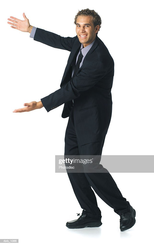 a young caucasian business man in a dark suit energetically gestures to the side : Stockfoto