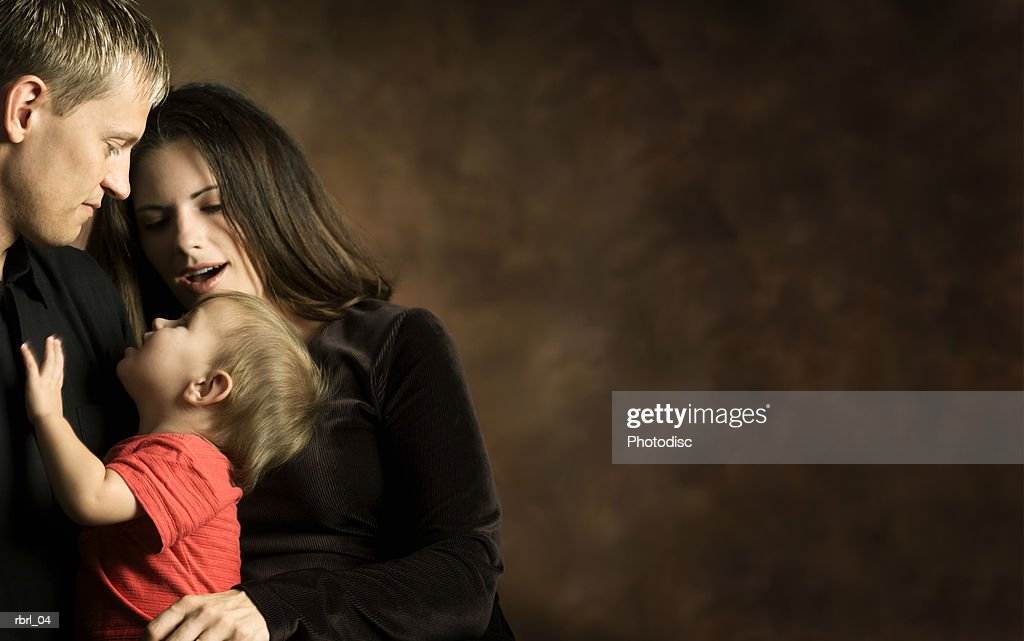a young caucasian couple play with their little baby girl : Stockfoto