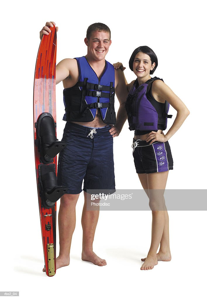 a young caucasian couple stand in lifejackets and swimming suits as the male holds a waterski and the two friends smile : Foto de stock