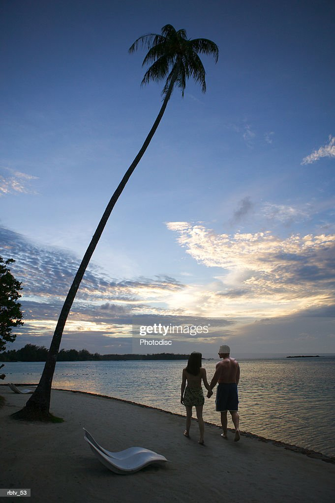 a young caucasian couple walk hand in hand on a beach while silhouetted by the sunset : Foto de stock
