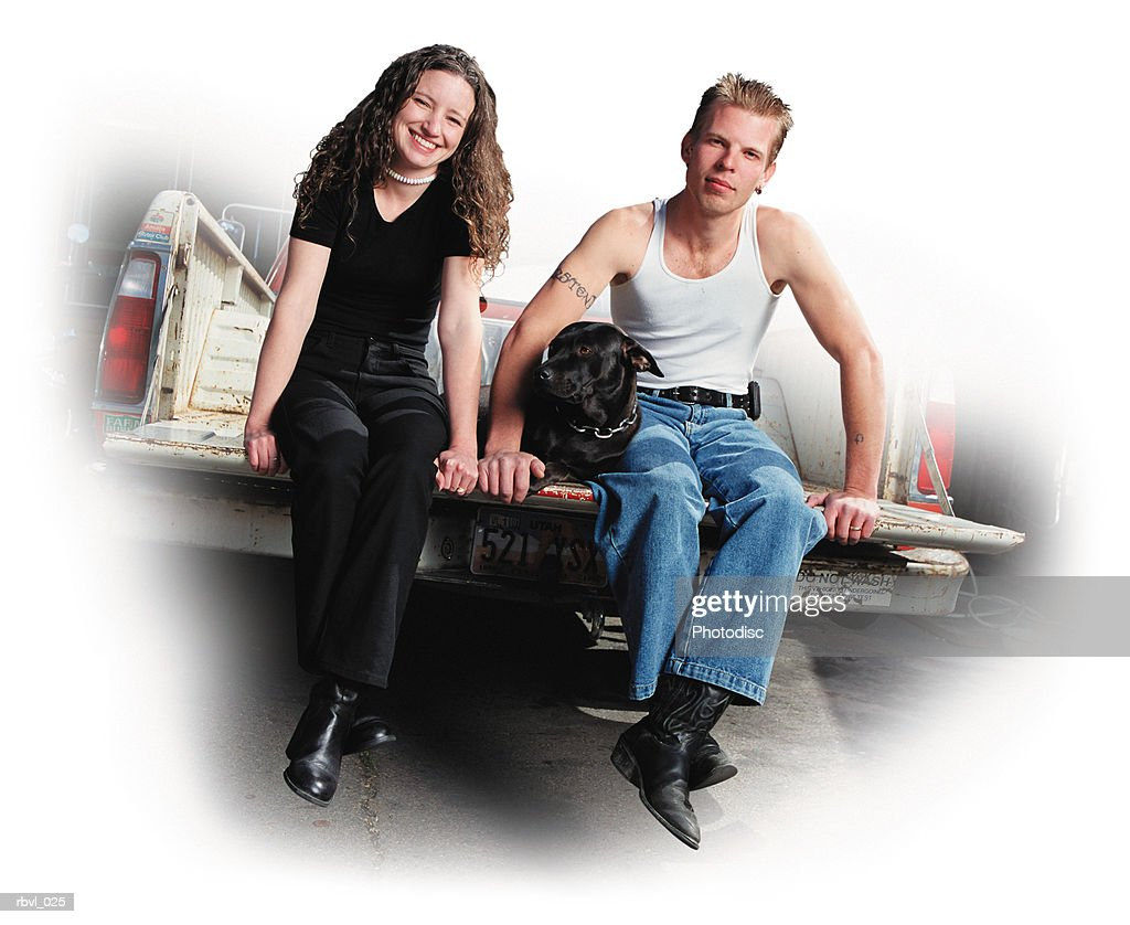 a young caucasian couple with thier black dog is sitting on the tailgate of an old pickup truck wearing jeans and a tank top and a black outfit along with black boots : Foto de stock
