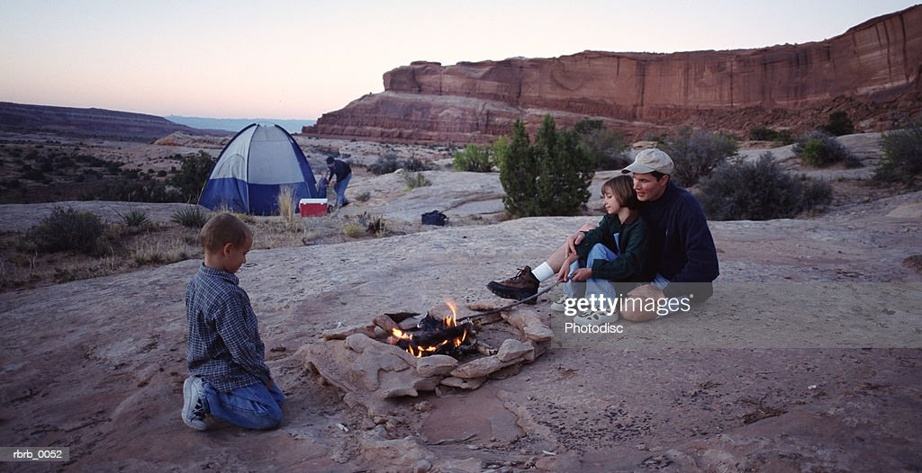 a young caucasian family gathers around the campfire : Stockfoto