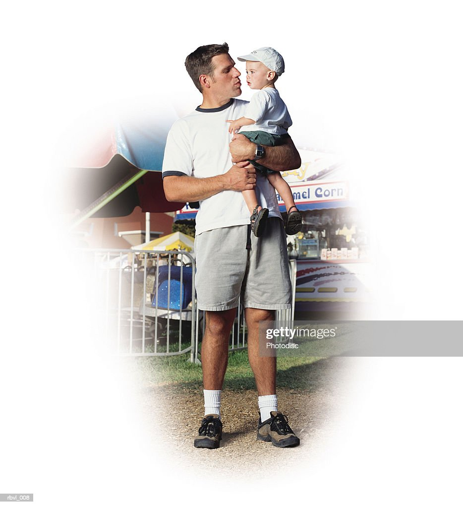 a young caucasian father in gray shorts and a white t-shirt is at a fair holding his baby son who is wearing a white baseball cap : Foto de stock