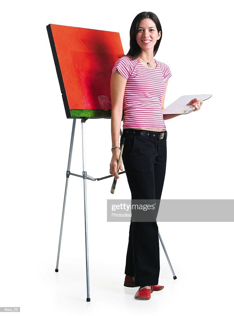 a young caucasian female artist stands with her painting while holding her paint and brush : Foto de stock