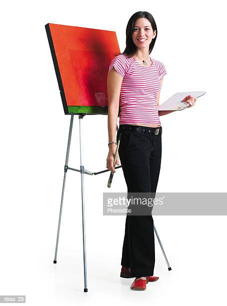a young caucasian female artist stands with her painting while holding her paint and brush