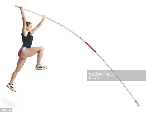 a young caucasian female athlete wearing a black and red uniform is starting a pole vault