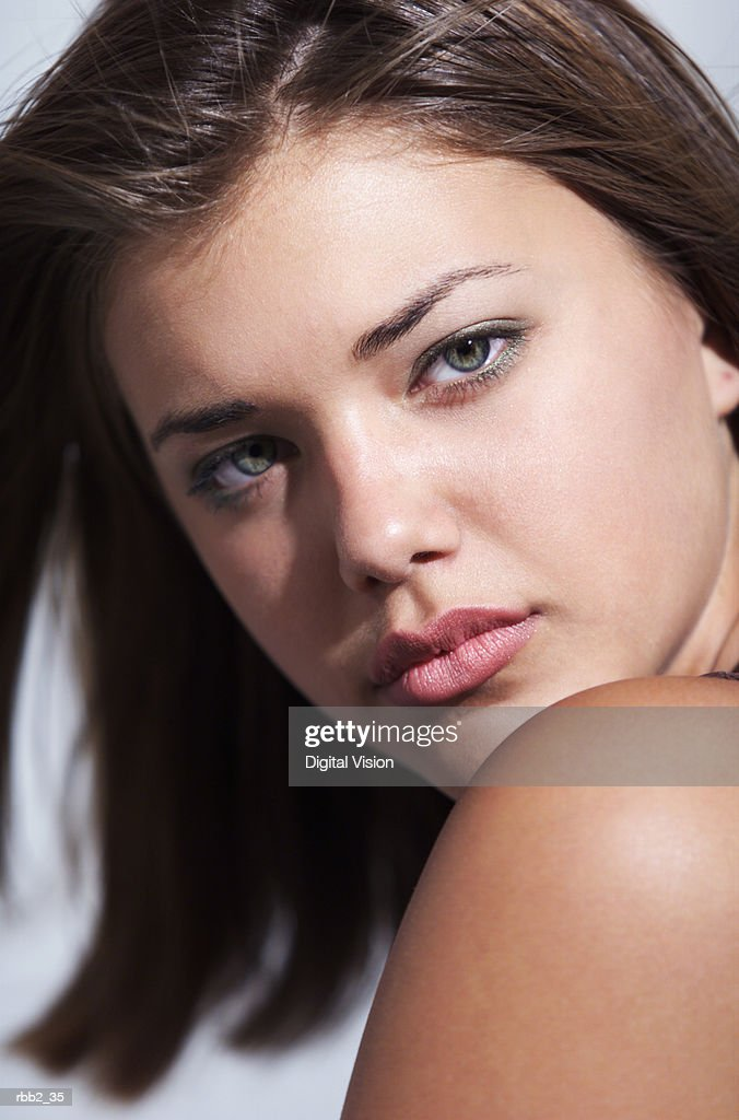 a young caucasian female brunette shows her bare shoulder as she stares seriously into the camera : Stockfoto