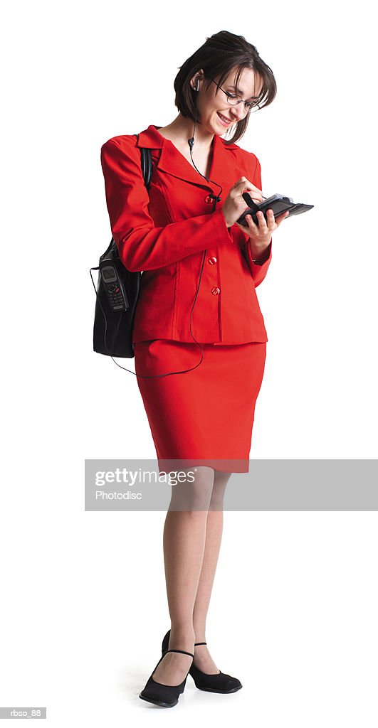 a young caucasian female business woman in a red dress writes in her personal organizer : Stockfoto