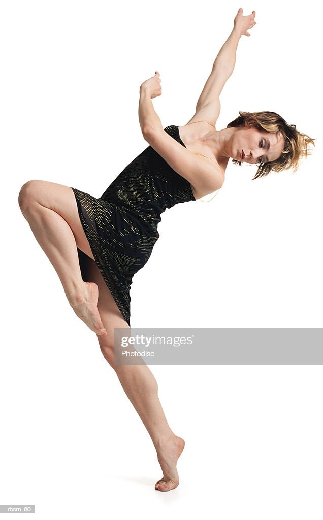 a young caucasian female dancer in a black dress balances herself on her toe and begins to turn her body : Foto de stock