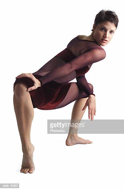 a young caucasian female dancer in a leotard stretches out her legs and contorts her body forward