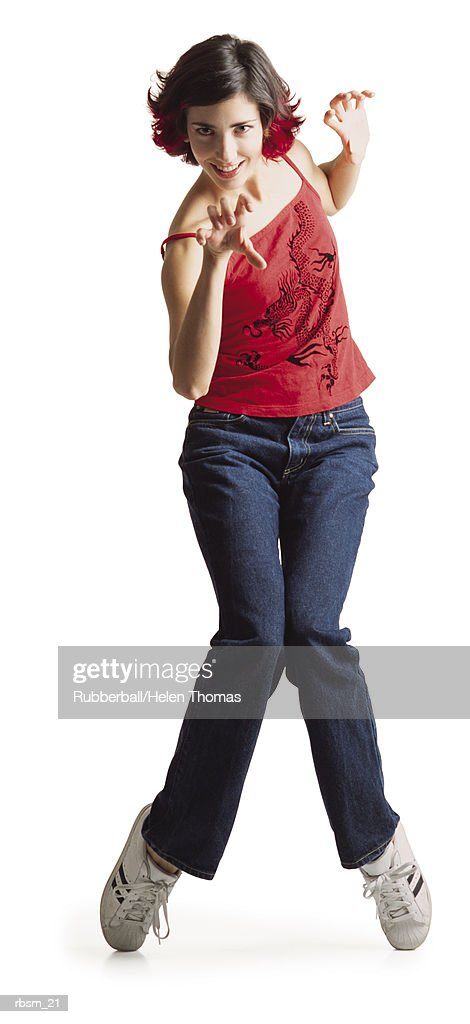 a young caucasian female dancer in blue jeans and a red tank top hops up on her toes and raises her hands like claws : Foto de stock