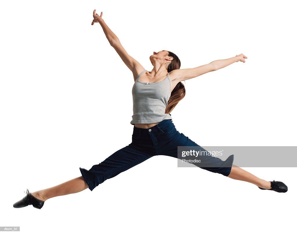 a young caucasian female dancer in jeans and a grey tank top jumps and flies through the air spreading all her limbs out : Foto de stock