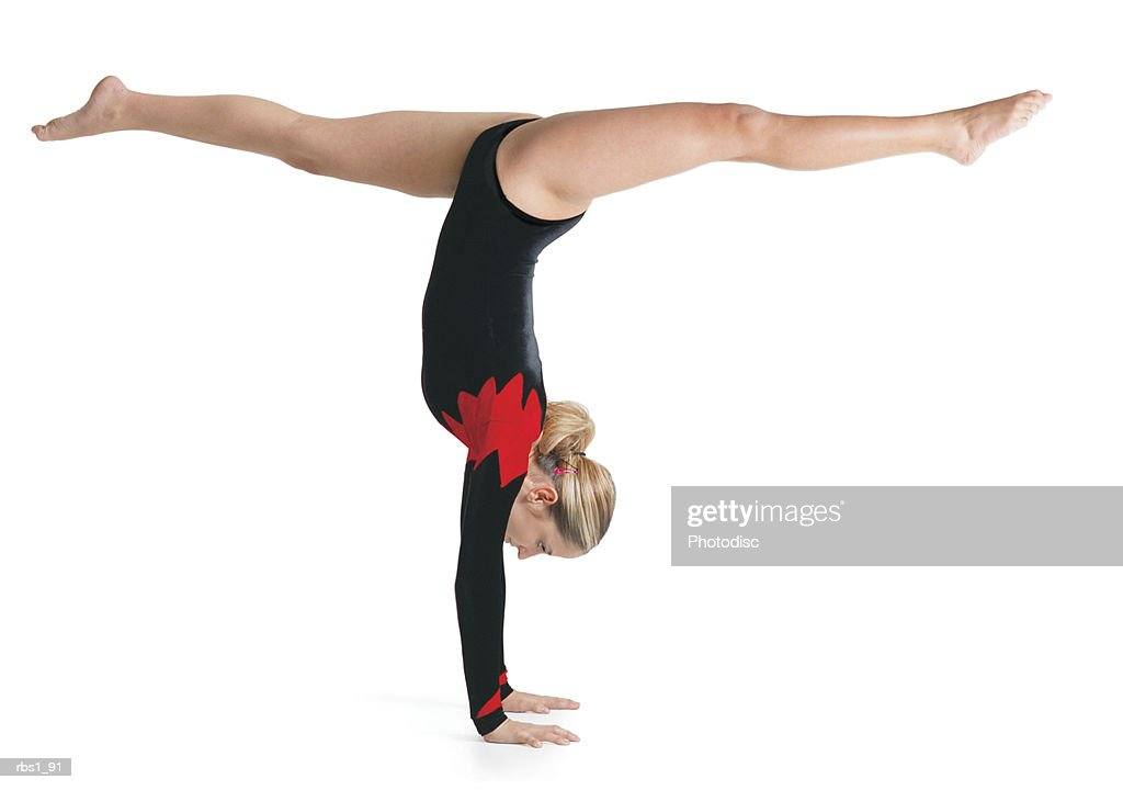 a young caucasian female gymnist in a red and black leotard does a handstand while doing the splits with her legs : Foto de stock