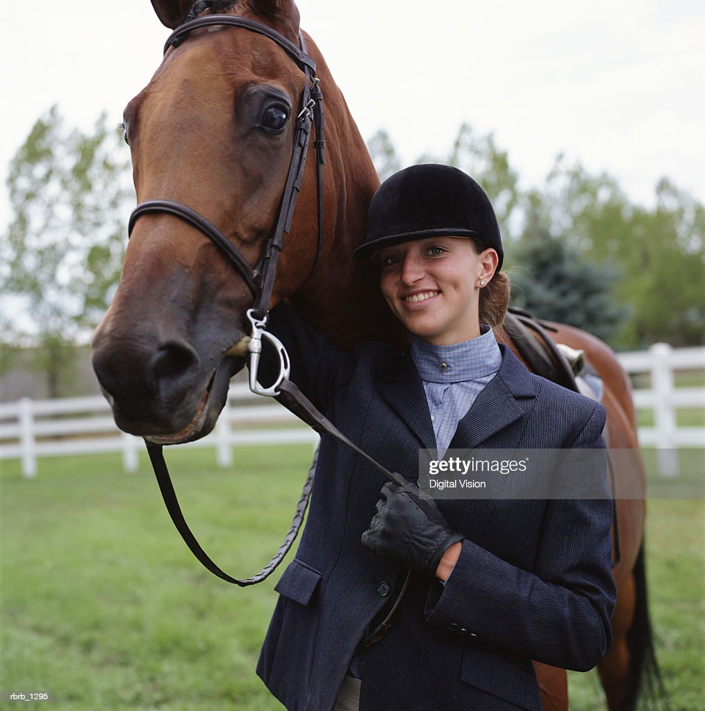 a young caucasian female horseback rider poses with her horse and smiles : Stockfoto