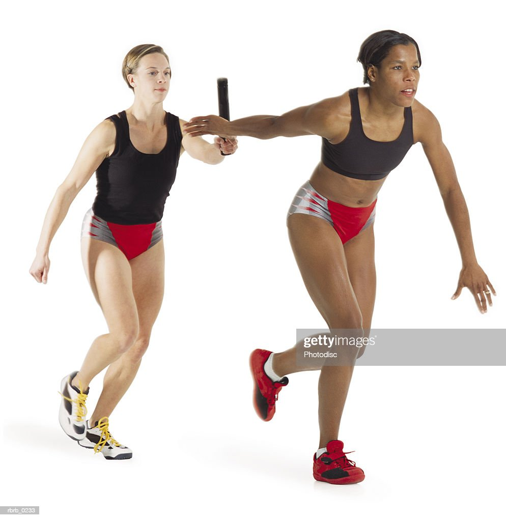 a young caucasian female runner passes the baton to her teammate a young african american female runner : Stock Photo