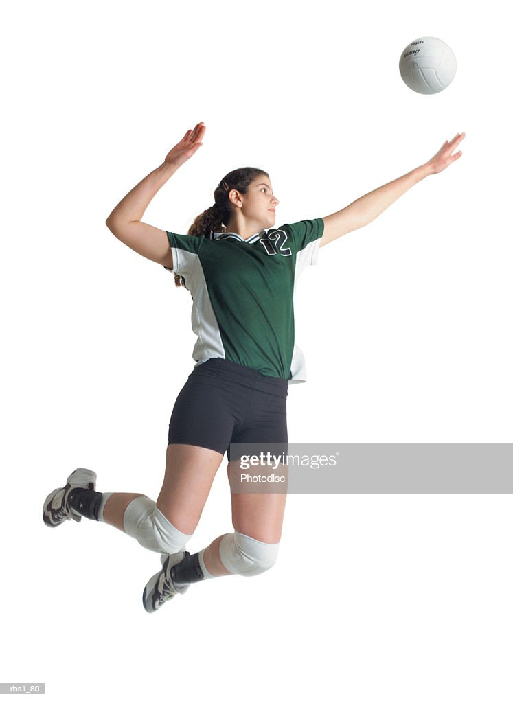 a young caucasian female volleyball player in a green and white jersey jumps high into the air to hit a ball : Foto de stock