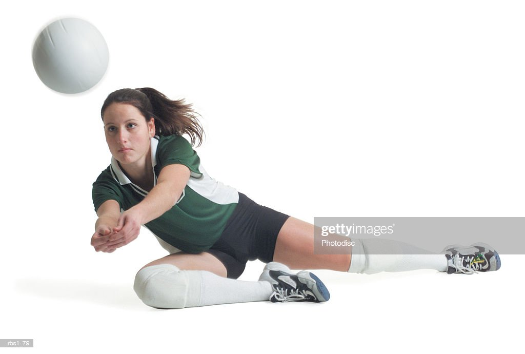 a young caucasian female volleyball player in a green and white jersey dives to the ground to hit a ball : Foto de stock