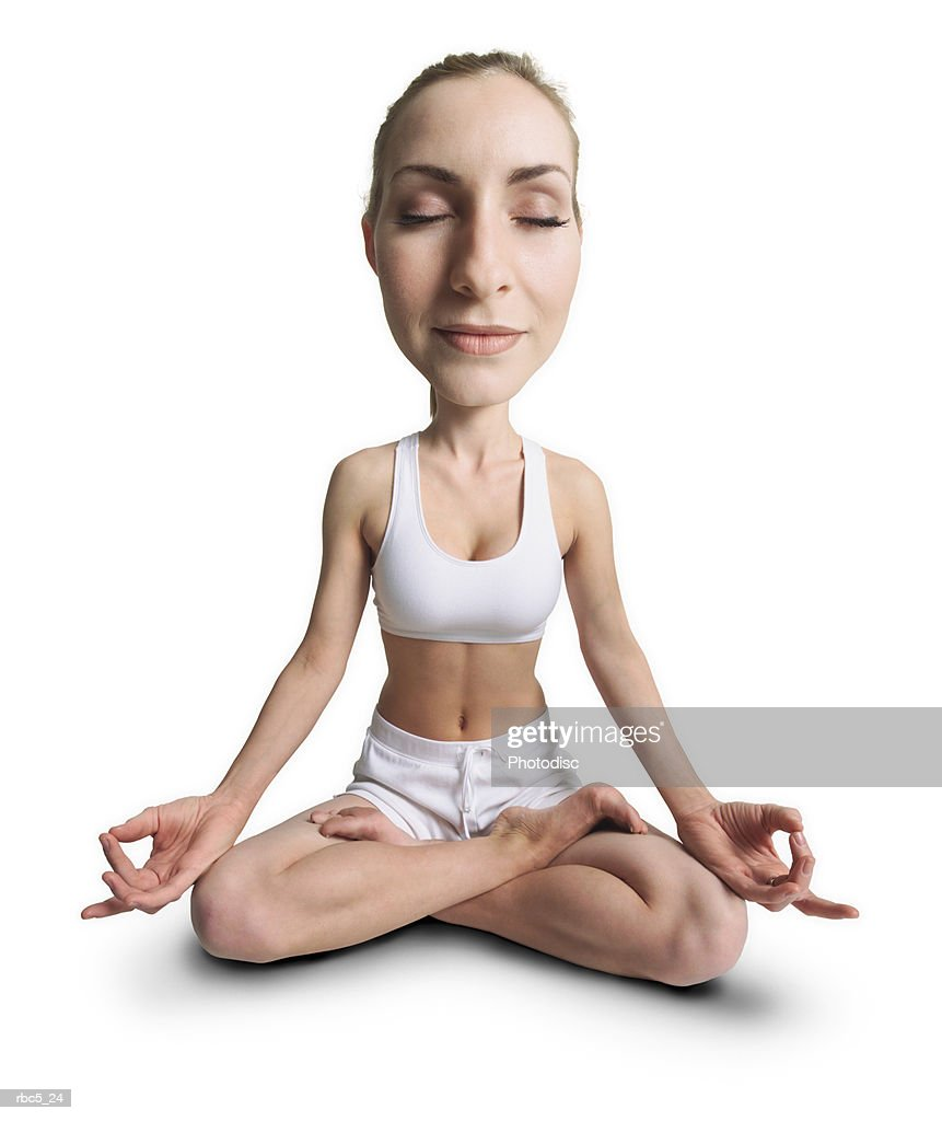 a young caucasian female wearing white work out clothes sits with her eyes closed and her legs crossed with her hands poised on her knees to meditate : Stockfoto