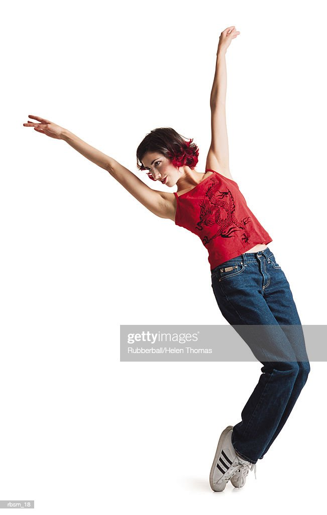 a young caucasian female with black hair with red tips and red tank top jeans and tennis shoes poses leaning to the left with arms in the air : Foto de stock