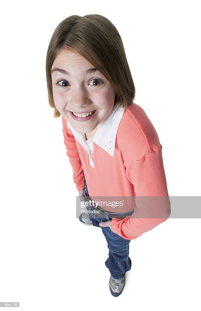 a young caucasian girl in jeans and a orange shirt puts her hands in her pockets and smiles up into the camera : Foto de stock
