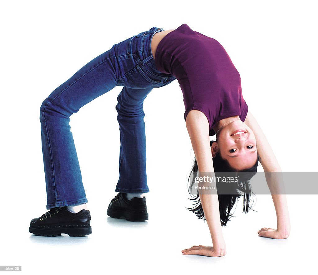 a young caucasian girl literally bends over backwards and smiles : Stockfoto