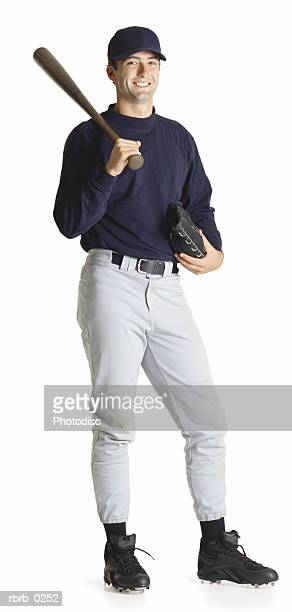 a young caucasian male baseball player in a blue shirt and hat holds his bat over his shoulder and smiles - ユニフォーム ストックフォトと画像