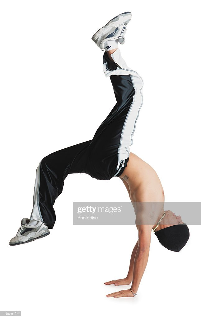 a young caucasian male breakdancer in black pants and no shirt and a knit cap is flipped upside down balancing on his hands with his legs in the air : Foto de stock