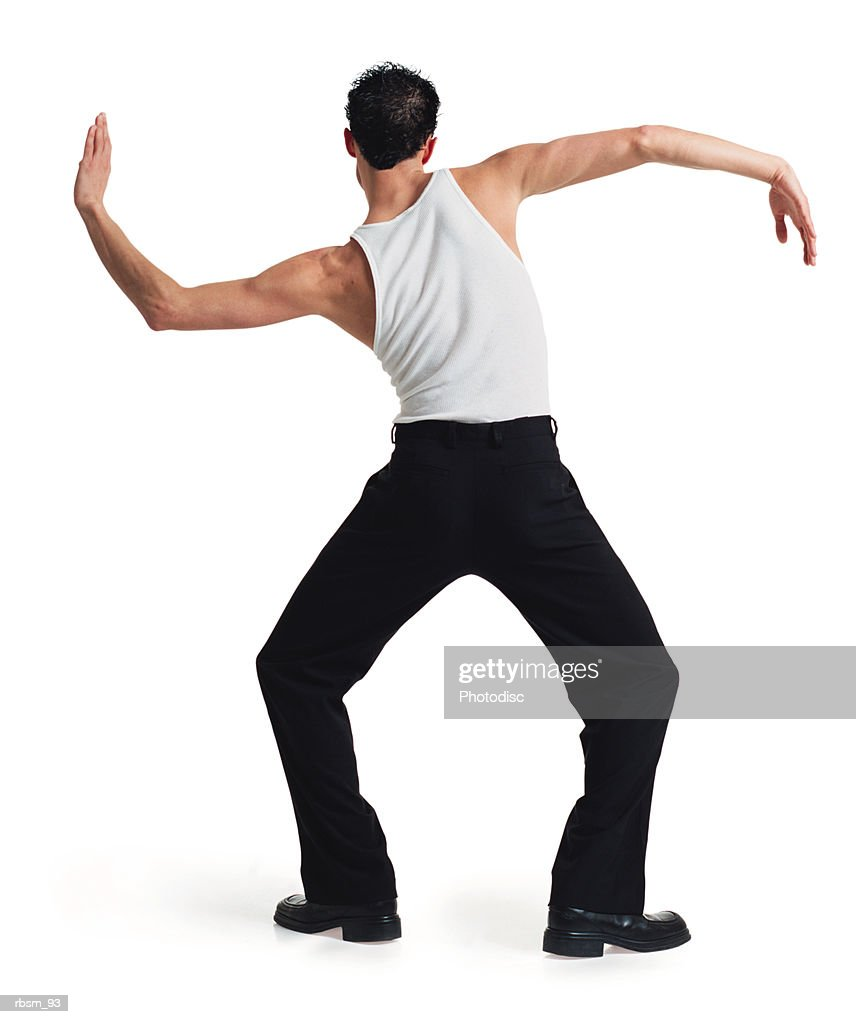 a young caucasian male dancer in black pants and white tank top stretches out and moves his arms with his back to the camera : Foto de stock