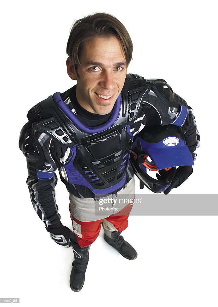a young caucasian male dirtbiker holds his helmet under his arm and smiles up into the camera : Foto de stock