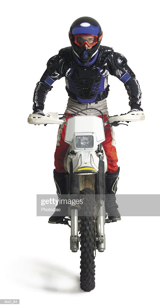 a young caucasian male dirtbiker sits upon his motorcycle and races forward : Stockfoto