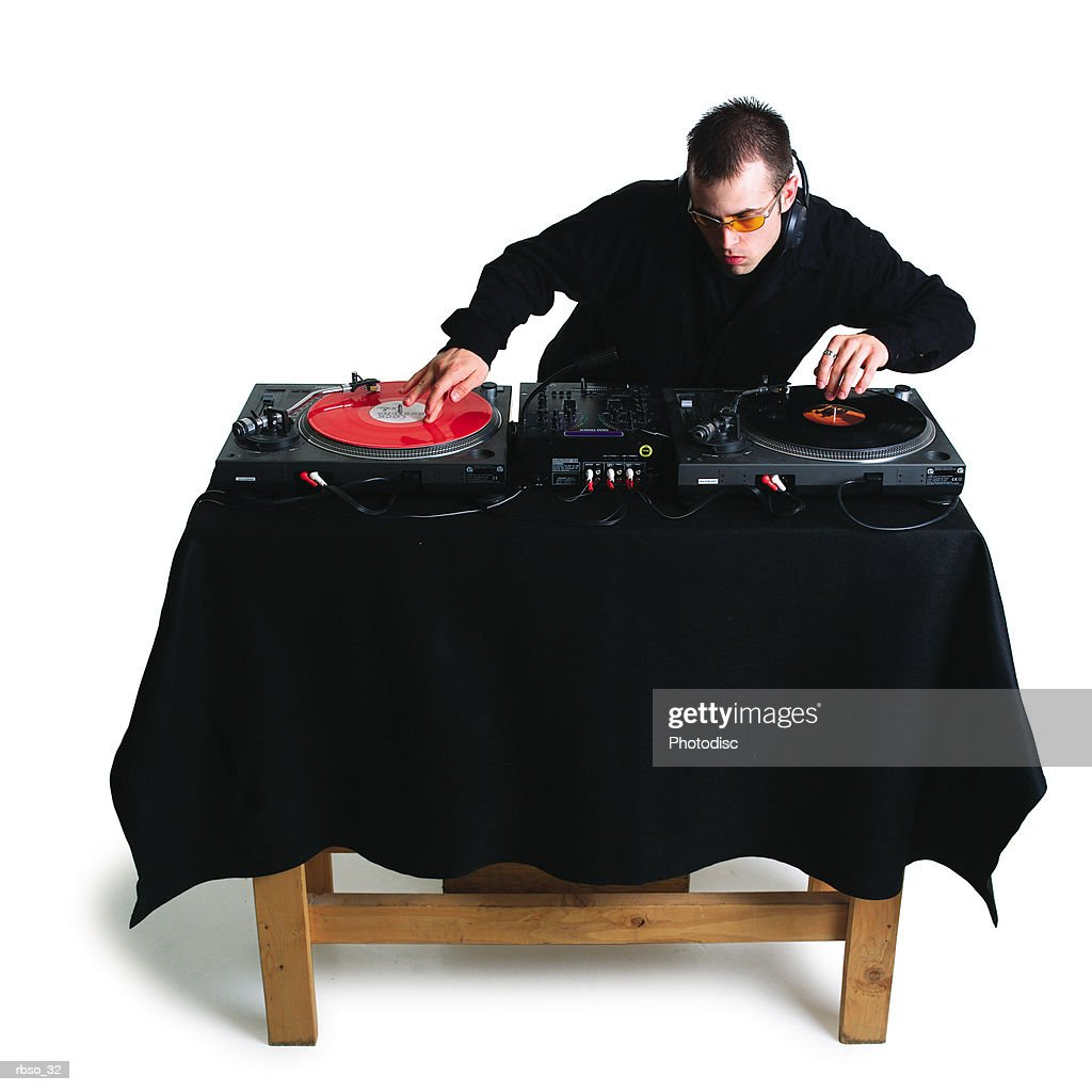 a young caucasian male disc jokey spins his records : Foto de stock