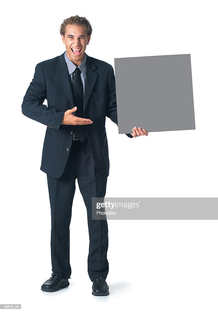 a young caucasian male in a dark business suit and tie holds a square sign to his side and gestures to it : Stockfoto