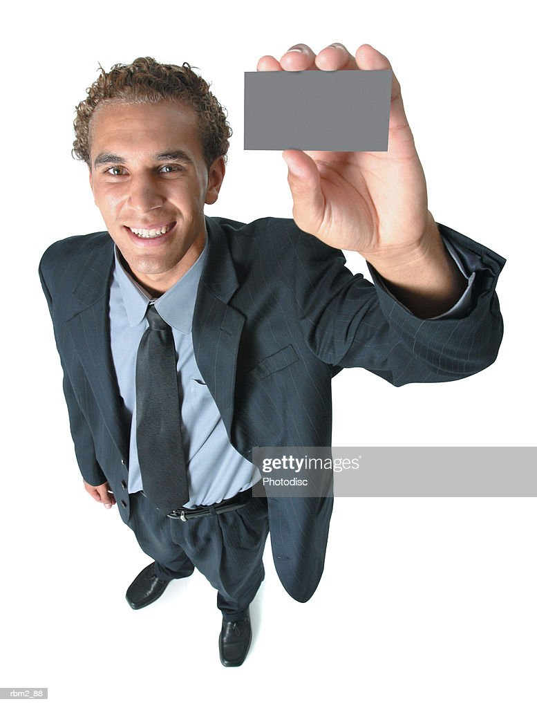 a young caucasian male in a dark business suit and tie holds up a  card as he smiles up at the camera : Stockfoto