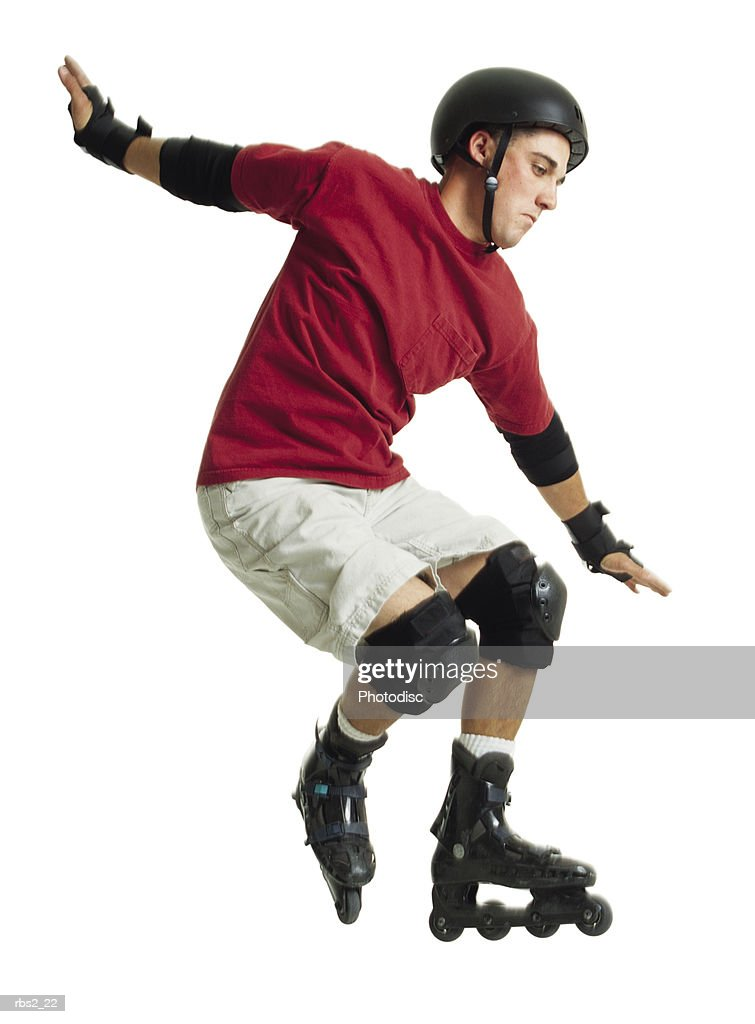 a young caucasian male in a red shirt and a black helmet rollerblades and jumps forward while balancing himself with his arms : Foto de stock