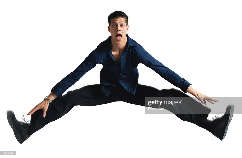 a young caucasian male in black pants and a blue shirt with long legs jumps into the air and does the splits while sticking out his tongue : Foto de stock