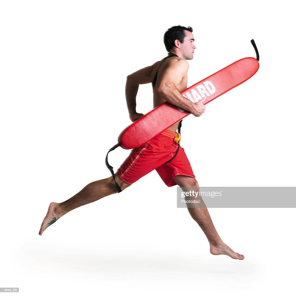 a young caucasian male lifeguard runs quickly with his rescue tube : Foto de stock