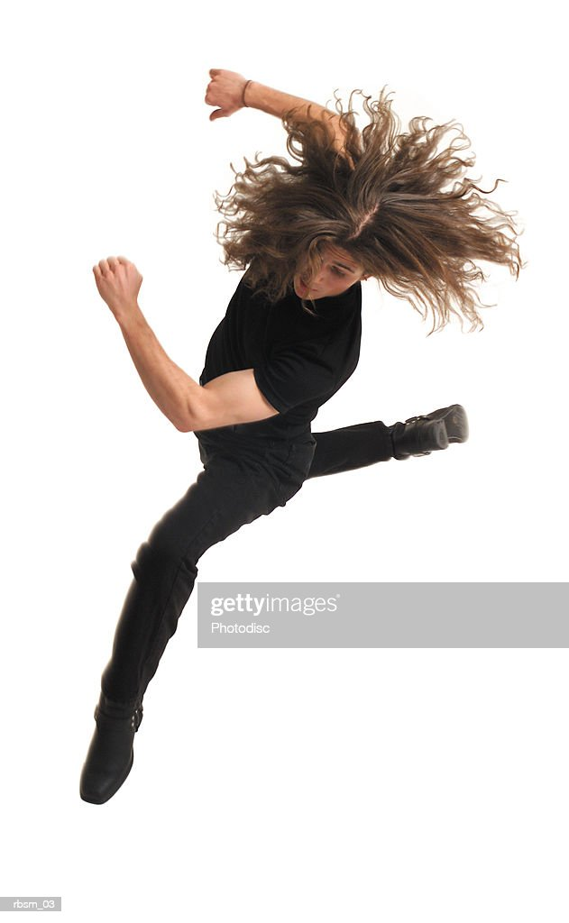 a young caucasian male modern dancer dressed in black with long hair jumps high into the air and spins around : Foto de stock