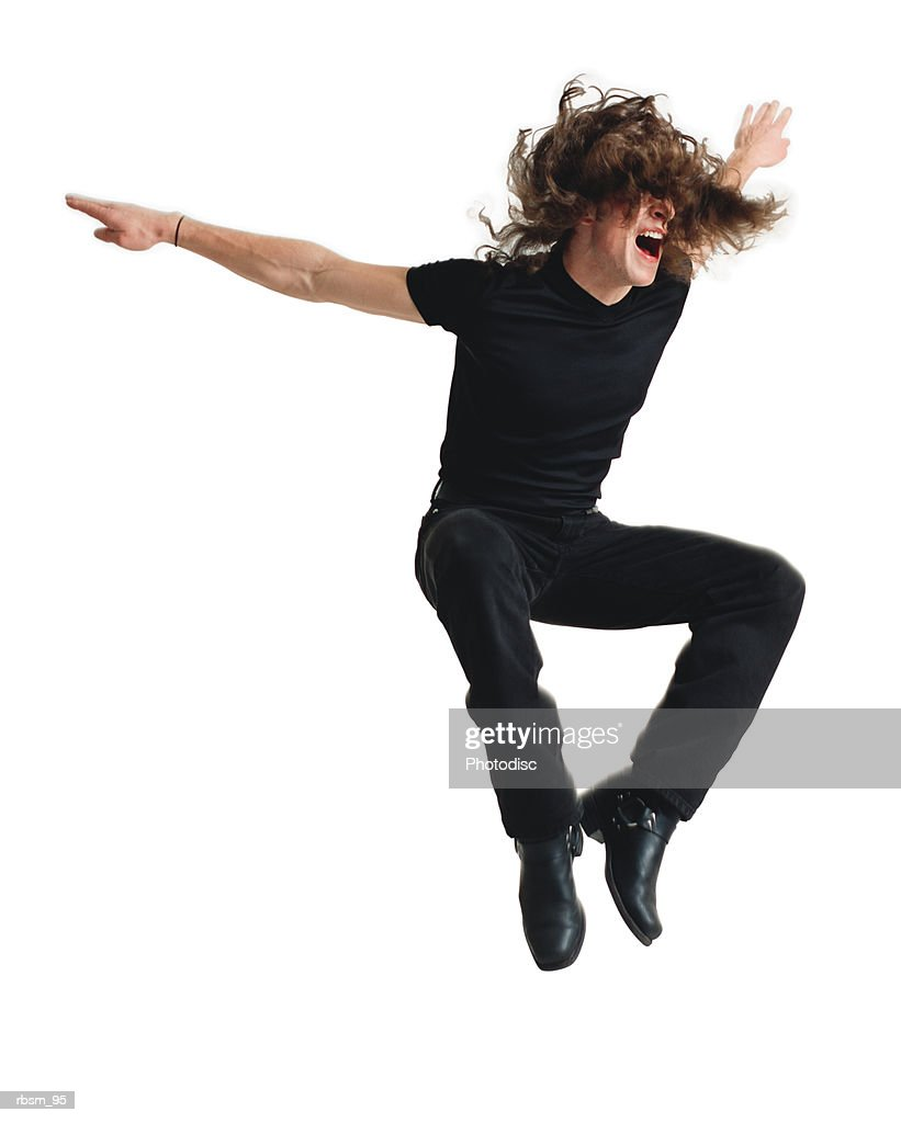 a young caucasian male modern dancer dressed in black with long hair jumps wildly into the air as he screams : Stock Photo