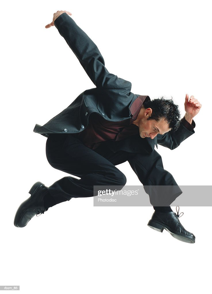 a young caucasian male modern dancer in a black suit jumps high into the air and flies downward with his aarm thrown back : Foto de stock